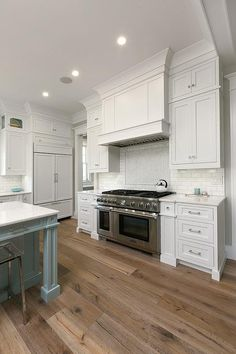Beautifully designed blue and white kitchen features a Thermador dual range is positioned on sawn oak wood floors between white shaker cabinets donning polished nickel pulls and white marble countertops located below a white paneled hood fixed on white subway tiles framing marble herringbone cooktop tiles.