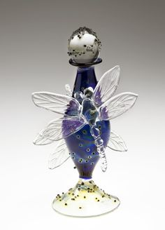 Dragonfly Bottle by Loy Allen. *Lampworked:lampwork* dragonflies, their wings dusted with shimmering *dichroic:dichroism* glass, perch on a lampworked perfume bottle accented with black *frit*.