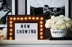 """For a fun twist on a movie-time staple, Michelle used white carnations to create a larger-than-life bowl of """"popcorn."""" Held in place by floral foam positioned at the bottom of the bowl, they add a pop of texture and just the right amount of whimsy to the mantel vignette."""