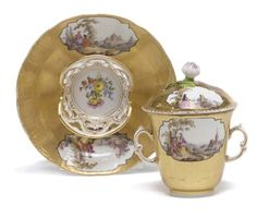 CIRCA 1770, BLUE SCEPTRE MARK AND IMPRESSED CYPHER TO STAND<br>In the Meissen style, the two-handled beaker, pierced socketed saucer and cover each painted with two shaped oval panels of figures at leisure pursuits in landscapes, each reserved within a black line on the burnished gold ground, the interior of the cup emplacement on the saucer with <I>deutsche Blumen</I>, the underside washed in pale turquoise green<br>5 1/2 in. (14 cm.) diameter, the saucer (3)