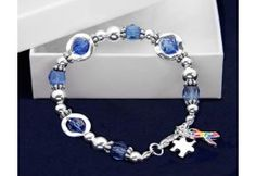 Silver Circles Autism Bracelet.  Each charm is sterling silver plated, one a puzzle piece and the other a multi- colored ribbon. Bracelet has a high quality feel. Bracelet is approximately 8 inches. (B-43-2)