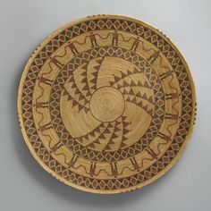 """A LARGE YOKUTS PICTORIAL COILED GAMBLING TRAY finely and tightly woven in sedge, redbud and bracken fern on a grass bundle foundation, with encircling friezes of human """"friendship"""" figures and rattle snake bands centering a radiant medallion.  diameter 28 in."""