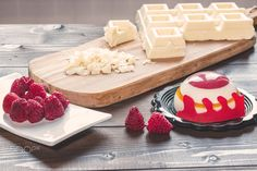 Raspberry cake and chocolate - Little raspberry cake on wooden table, near raspberries and white chocolate on wooden chopping board