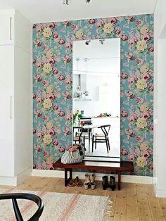 Parede decorada com espelho centralizado.