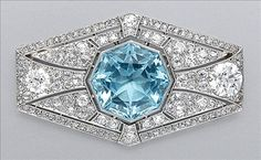Aquamarine and Diamond Brooch  Platinum, the elongated hexagonal pierced mount centering one octagonal-cut aquamarine, approximately 14.00 cts., further enhanced by 2 old European-cut diamonds, approximately 2.40 cts., set throughout with 128 old-mine cut diamonds, approximately 3.45 cts., circa 1920, approximately 11.7 dwt.