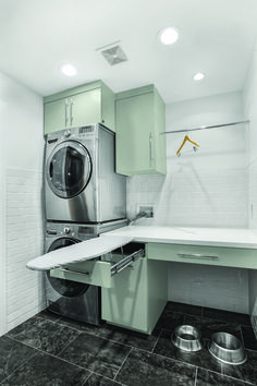 In the utility room, stacked washer and dryer conserves space and a hideaway ironing board makes quick work of wrinkles.