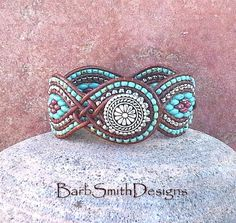 The Twisted Sister in Turquoise Shes the most desired girl in the bunch! What makes this sister twisted is the leather weaves that give this cuff her shape! This unique 5-row cuff bracelet features curves of Nickel Plate and Opaque Picasso Turquoise and Coral Red beads, surrounded by coordinating seed beads. It is hand-stitched on Distressed Light Brown Indian Leather Cord and fastens with a 5/8 silver Bali button surrounded by a double beaded button loop. Finished Size: 6 3/4 Fits Wrist…