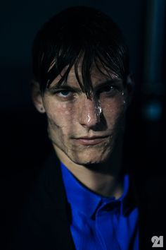 Portrait of a male model in low light wearing blue and wet hair