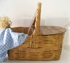 vintage picnic basket with green checked fabric with baguette bread x2 sticking out with some flowers - white