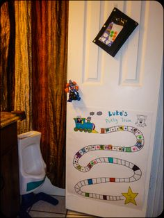 Potty train chart.  * Picture of himself inside the train *Colored spots are for a  prize (he plays with playdoh).  *Made round dots into poopoo stickers.  *Cear tape on the track in case we need to peel the stickers off and start over.  *Sticker bag up high for easy access.  *Foam cleaner on the urinal drain & he washes it away with his pp. *Superhero on the door for when he sits on the big toilet for #2. *Urinal found at resale shop (love it)