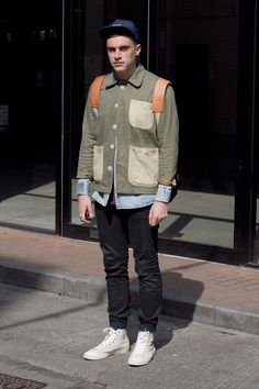 Coggles London Street Style with green jacket with contrasting pockets and buttons, blue shirt, black jeans, white trainers, navy cap and tan rucksack. #streetstyle #fashion