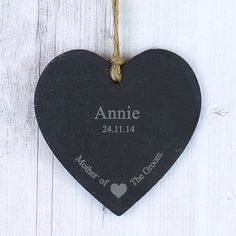 Personalise this Mother of the Groom Slate Hanging Heart with one line of 12 characters and one line of 20 characters. The design features a sweet heart motif at the bottom of the slate product, with the fixed text 'Mother of the Groom'. The heart has a piece of natural, rustic string which enables this item to be hung up.  PLEASE NOTE- Each slate piece will be unique as the item is cut by hand. Due to the nature of slate there will be some differences in the stone (such as texture, cut and…