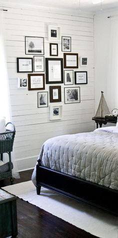 cluster of frames and wood wall and dark floor and rug under bed and bedding and sailboat and old timey crib and white walls. I think I like this room.