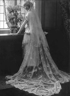 1920's Bride wearing a very long wedding veil made of fine lace.