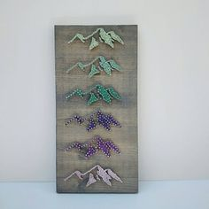 This beautiful string art is inspired by the mountain ranges of the Pacific Northwest.  7.5 x 16 inch lodge pole Pine board stained grey.  Stainless steel wire nails with a color fade from light green to light purple string pop against the grey stained pine.  A perfect combination of rustic charm and simple elegance for your get away cabin or everyday wall decor to show your love of the outdoors.  All pieces come with a sawtooth hanger mounted to the back, ready to hang.  All pieces are…