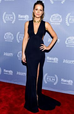 KATE BECKINSALE in a low-cut, v-neck sleeveless gown with side cut-outs and a thigh-high slit, which she paired with a gold statement necklace and her signature ponytail at the 2016 San Diego International Film Festival in San Diego.