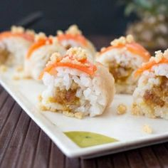 """A healthy, whole-food """"sushi"""" made with coconut sticky rice, pineapple date filling, and """"papaya sashimi"""" on top."""