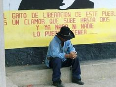 Old El Salvadoran cowboy sitting in front of a mural of the late Fr. Oscar Romero.