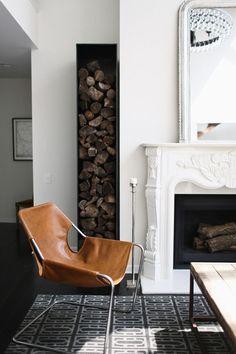 cheminée classique décorée de moulures et dotée d'une niche de rangement bois de chauffage