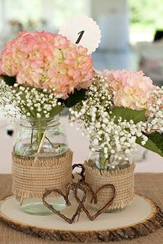 With Dahlias and baby's breath for center pieces.... Top 5 Mason Jar Ideas - Take Center Stage: Wedding Table Numbers. Mason jars make wonderfully simple centerpiece containers. One easy way to make your flowers a focal point is by placing them in these understated jars. Embellish them with a little burlap or colorful ribbon to go with your theme. Elevate them on wood slabs, vintage cake stands, or line them up along a banquet table. Photo from Limefish Studio.