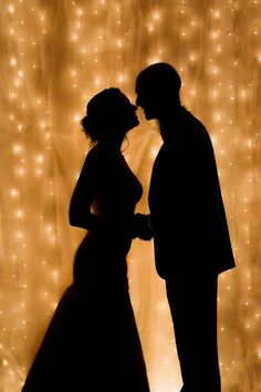 perfect wedding silhouette. love the white twinkle lights as a background.