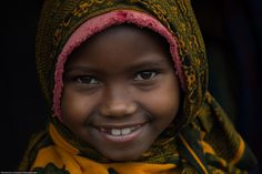 A young Iraqw girl smiles at her new visitors. Photo by Zach Pendley