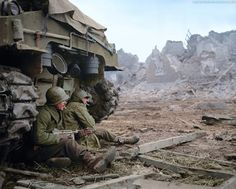 WW2-Two US soldiers from the C Company, 36th Infantry Regiment, 3rd Infantry Division, take refuge behind a Sherman M-4 tank in Geich, Germany, on December 11, 1944.