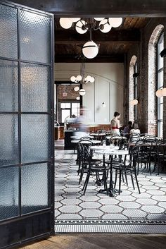 Industrial inspired restaurant space with exposed brick, exposed wooden beams and original tiles floors