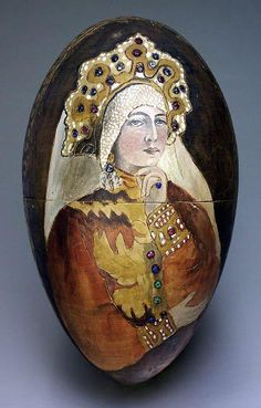A large and rare carved wooden Easter egg painted with a Russian beauty, inlaid with faceted colored glass, period of Nicholas II.   Height 6 1/2 in. (16,3 cm)   Diameter 3 3/4 in. (9,6 cm)