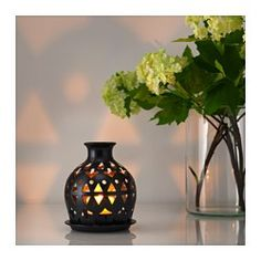 The warm light from the candle shines decoratively through the pattern on the lantern.