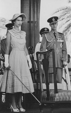 English- Queen Elizabeth in Aden Colony, 1954, wielding a spadroon in preparation to knight Claude Pelly and Sayyid Abubakr. Prince Phillip is visible at the side. This was the first public investiture of the tour.