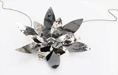 three layers of forged, polished and oxidized silver mounted to a goth version of a cherry blossom