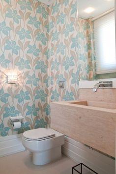 O lavabo da área social foi totalmente envolvido por papel de parede com uma delicada estampa floral. A bancada, em travertino romano, estab...