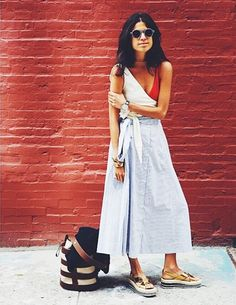 Leandra Medine of the Man Repeller wears a tie-front top, maxi skirt, flat-form metallic sandals, printed sunglasses and oversized accessories