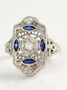 18 karat white gold filigree ring with a center diamond at 0.15 carat VS2 clarity K-L color and four small marquise sapphires at 0.20 carat total weight with milgrain detailing, circa 1920. Size 6.5.