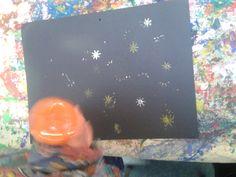 Neem verschillende kleuren verf en stempel op een donker vel papier.
