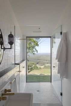Bathroom: walk-in shower with floor-to-ceiling window with a view, brushed/matt brass taps and towel rail, white handmade wall tiles, robe hook, white concrete floor