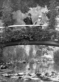 Claude Monet stands on the Japanese footbridge he painted throughout the years, 1922.