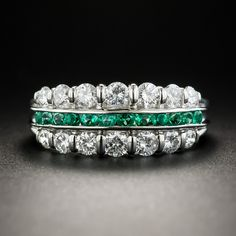 A slender row of small round faceted vibrant crystalline green emeralds is bordered on each side by a row of sparkling white round brilliant-cut diamonds (totaling .88 carat), in this bright and beautiful band ring rendered in gleaming platinum. 5/16 inch, Currently ring size 6 1/4.