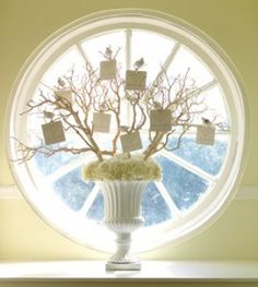Branching Out  A white urn filled with hydrangea blossoms is topped with bare branches where faux birds are perched, holding guests' butler (escort) cards.