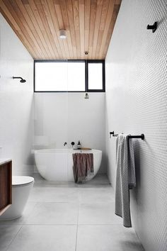A renovated worker's cottage that maximises space and style Penny-round mosaics from Tiento Tiles and a Kado 'Lux Petite' bath from Reece amp up the luxury in the main bathroom, while timber panelling on the ceiling increase's the room's sense of space Wooden Bathroom, White Bathroom, Master Bathroom, Bathroom Canvas, Bathroom Mirrors, Simple Bathroom, Bathroom Cabinets, Restroom Cabinets, Ikea Bathroom
