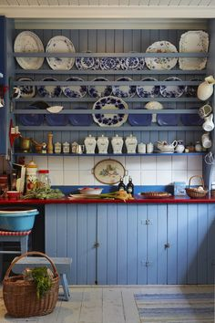 Country blue kitchen with an enormous plate rack.
