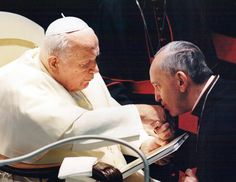 Jorge Mario Bergoglio, Archbishop of Buenos Aires, (now Pope Francis) right, kisses the hand of Pope John Paul II during a ceremony at the Vatican.