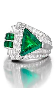 An Art Deco emerald and diamond ring, circa 1925. Centring a triangular-shaped step-cut emerald... accented by calibré-cut emeralds, old European and baguette-cut diamonds, set overall in an asymmetrical mount ... in platinum | Bonhams, New York. Auction 24183 Lot 37