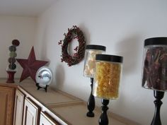 old jars on dollar store candlesticks filled with cheap beads, seaglass, rocks above kitchen cabinets Above Cabinet Decor, Decorating Above Kitchen Cabinets, Above Cabinets, Cheap Kitchen Cabinets, Kitchen Jars, Cabinet Ideas, Kitchen Ideas, Kitchen Decor, Country Primitive