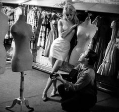 """1958:  Dress designer Jacques Esterel (1918-1974) established his couture house, Jacques Esterel, in 1953. The first years were especially successful as Esterel contributed to a playful fashion spirit, illustrated by the """"Vichy"""" bridal gown which he designed for French actress Brigitte Bardot.  In the early 1970s Esterel created his most well-known and talked-about collection, the """"unisex"""" line, presenting clothes designed for both men and women."""