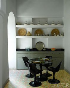 The kitchen counter is black granite, the cabinetry is custom, the pottery includes traditional Moroccan tagines, and the floor tiles were inspired by a pattern in an adjacent building.