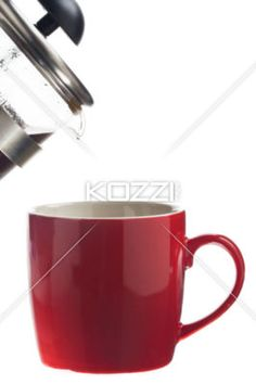 serving coffee in a red cup. - Close-up shot of pouring coffee into red cup over white background,