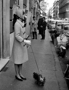 Audrey Hepburn photographed with her Yorkshire Terrier byMarcello Geppetti after shopping at a grocery in Rome (Italy), in November 1961.Audrey was wearing:Coat: Givenchy (of wool, white background with a weft in the navy blue color, double-breasted with buttons of resin in the navy blue color, with collar à revers and sleeves with height above the wrists, length below the knees, liner of silk taffeta in the navy blue color, of his collection for the Autumn/Winter 1961/62).
