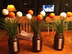 "Mason jars painted as footballs and styrofoam baseballs and basketballs for a masculine sport themed ""floral arrangement"" centerpiece"